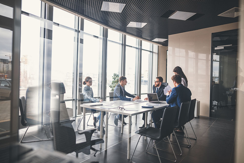 Business team in conference room around table discussing technology strategy